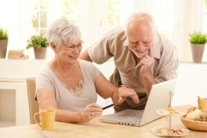 Happy older couple doing online shopping, laughing wife pointing at screen of laptop computer.